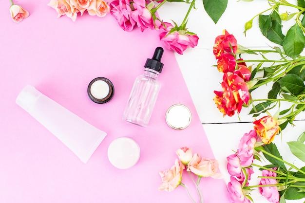 Kosmetyki do pielęgnacji skóry w ramce świeżych róż.