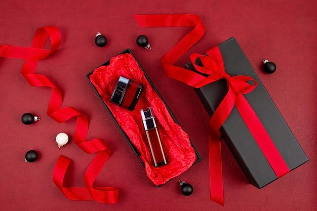 Kosmetyki do pielęgnacji twarzy kobiety zapakowane w czarne pudełko z czerwoną wstążką