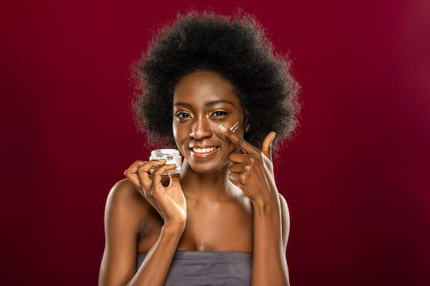 Kosmetyki do skóry. radosna miła kobieta trzyma butelkę z kremem podczas nakładania jej na twarz