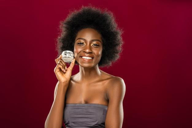 Kosmetyki do twarzy. miła wesoła kobieta uśmiecha się do ciebie, pokazując butelkę z nowym kremem