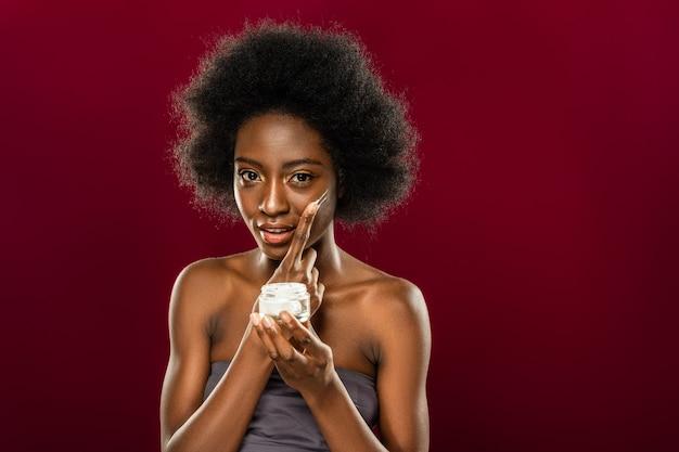 Kosmetyki do twarzy. pozytywnie zachwycona kobieta za pomocą organicznego kremu do twarzy stojąc przed czerwoną ścianą