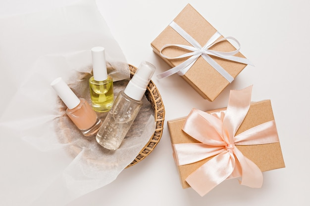 Kosmetyki ekologiczne i prezenty na święta. płaska świecąca, widok z góry butelka z pompką z przezroczystego szkła, słoik na pędzle, słoik na serum nawilżające w papierowym koszu na białym tle. kosmetyki naturalne spa