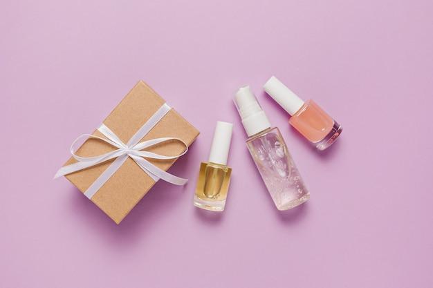 Kosmetyki ekologiczne i prezenty na święta. płaska, ułożona, widok z góry przezroczysta szklana butelka z pompką, słoik na pędzle, słoik na serum nawilżające na fioletowym tle. kosmetyki naturalne spa
