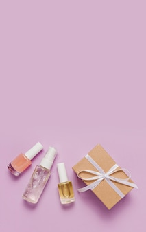 Kosmetyki ekologiczne i prezenty na święta. płaska, ułożona, widok z góry przezroczysta szklana butelka z pompką, słoik na pędzle, słoik z serum nawilżającym na fioletowym tle. kosmetyki naturalne spa