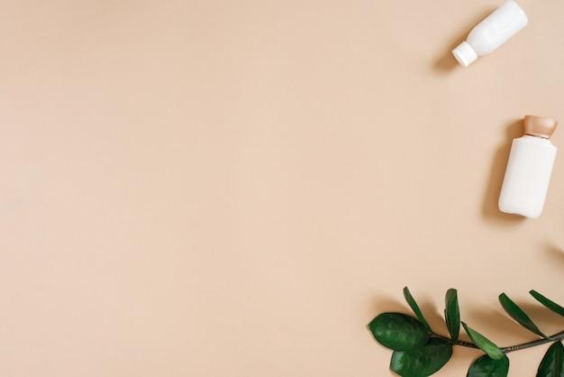 Kosmetyki ekologiczne z zieloną gałązką zamiokulkas i butelkami kremów na beżowym tle z copyspace, widok z góry