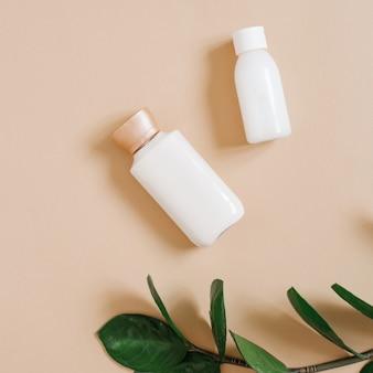 Kosmetyki ekologiczne z zieloną gałązką zamiokulkas i butelkami kremów na beżu