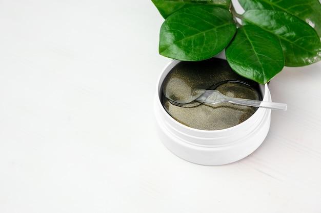 Kosmetyki hydrożelowe plastry oczu i zielona gałąź z liśćmi na białym tle z miejsca na kopię. koncepcja pielęgnacji skóry i kosmetologii. liftingująca przeciwzmarszczkowa maska kolagenowa.