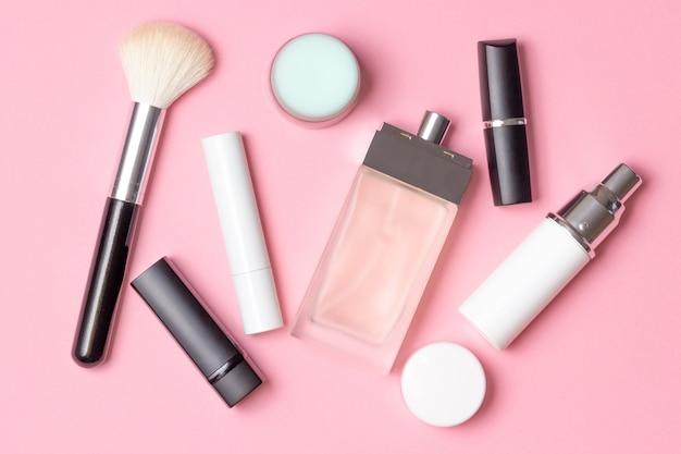 Kosmetyki i akcesoria damskie na różowym tle: perfumy, krem, szminka, pędzel do makijażu. koncepcja mody i urody