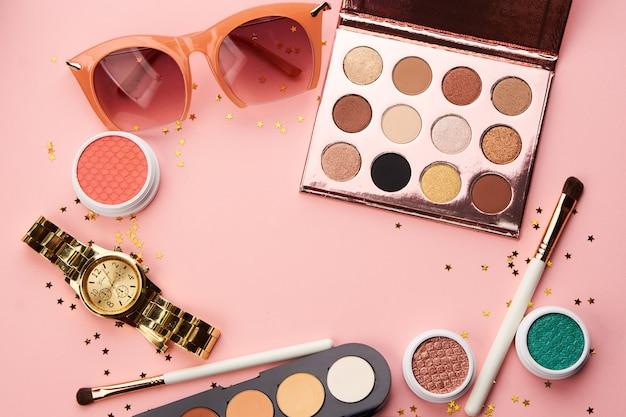 Kosmetyki i biżuteria na różowym stole