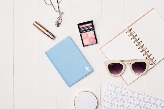 Kosmetyki i elementy mody kobiet na stole z aparatem i paszportem. widok z góry
