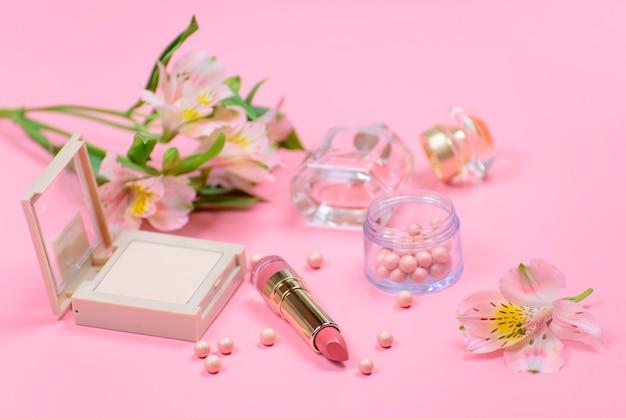 Kosmetyki i kwiaty na różowym tle