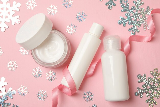 Kosmetyki i płatki śniegu na różowym tle