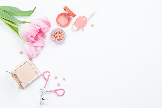 Kosmetyki i różowe tulipany na białej powierzchni