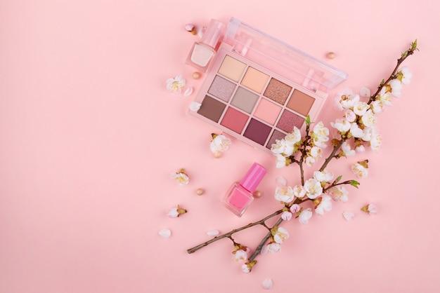 Kosmetyki i sakura oddział na różowej ścianie. koncepcja piękna, leżał płasko.