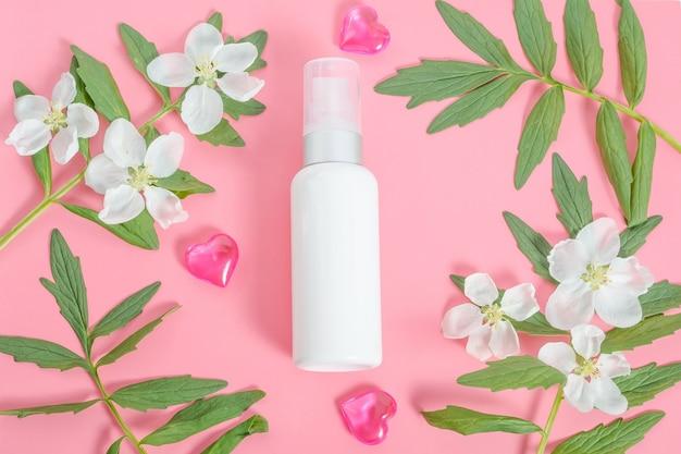 Kosmetyki jako prezent na walentynki, biała tubka kremu w ramce z kwiatów i liści na różowym tle