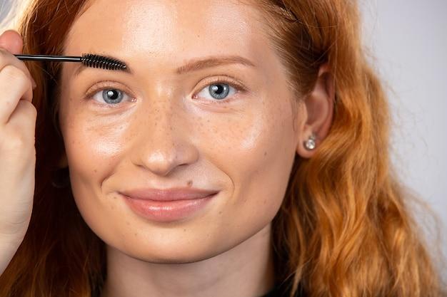 Kosmetyki kosmetyczne. close-up piękna rudowłosa dziewczyna z piegami, która jest farbowana brwiami. modna modelka o miękkiej skórze, doskonały makijaż. wysokiej jakości zdjęcie