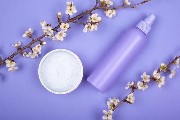 Kosmetyki kremowe i gałązki kwitnące na fioletowym tle. koncepcja pielęgnacji skóry, uroda.