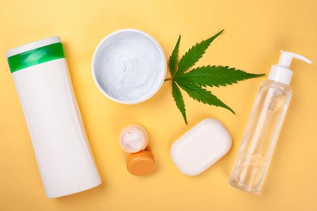 Kosmetyki na bazie olejków marihuany, konopie do pielęgnacji skóry na żółtym tle.