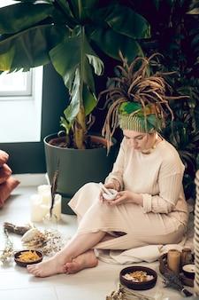 Kosmetyki naturalne. młoda kobieta siedzi w ogrodzie i przygotowuje kosmetyki naturalne