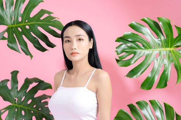 Kosmetyki naturalne. zmysłowa azjatka na tle tropikalnych liści, patrząca w kamerę na różowo