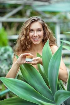 Kosmetyki organiczne. kobieta w pobliżu zakładu, trzymając słoik kremu do twarzy