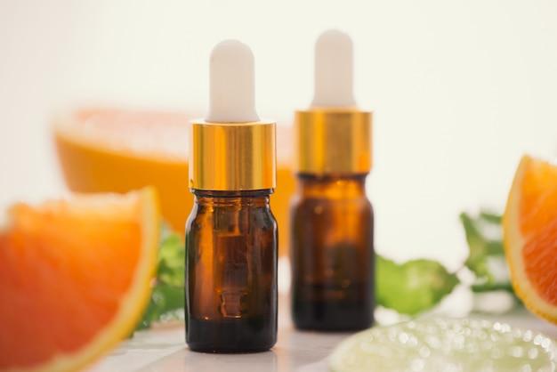 Kosmetyki organiczne z ekstraktami ziołowymi cytryny, pomarańczy, mięty na jasnym tle
