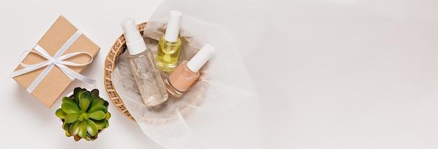 Kosmetyki organiczne z roślinami i prezentami na święta. płaska świecąca, widok z góry butelka z pompką z przezroczystego szkła, słoik na pędzle, słoik na serum nawilżające w papierowym koszu na białym tle. kosmetyki naturalne spa