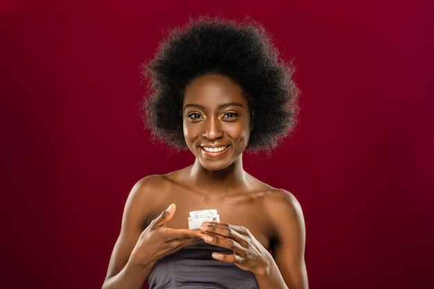 Kosmetyki organiczne. zachwycona pozytywna kobieta uśmiecha się do ciebie trzymając butelkę ze śmietaną