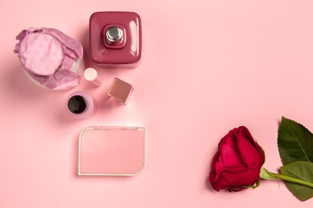 Kosmetyki, perfumy i róża. monochromatyczna stylowa i modna kompozycja w różowym kolorze na ścianie studia. widok z góry, układ płaski.