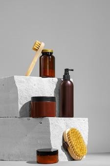 Kosmetyki pielęgnacyjne i szczotka do masażu na szarym tle