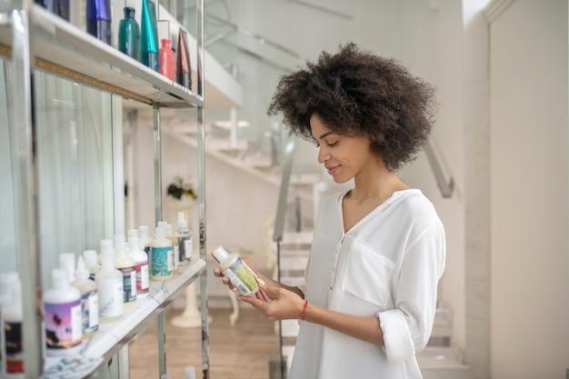 Kosmetyki pielęgnacyjne. młoda uśmiechnięta ładna dziewczyna zainteresowana produktem kosmetycznym stojącym w holu centrum urody