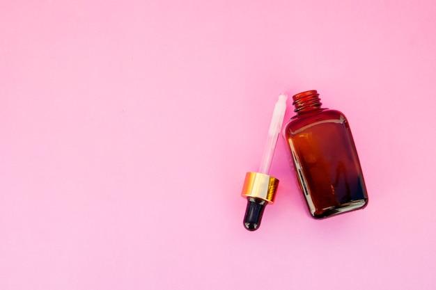 Kosmetyki spa, terapia salonowa. szklana butelka na różowo. copyspace.