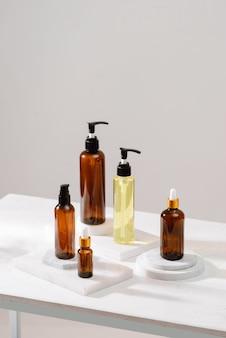 Kosmetyki spa w brązowych szklanych butelkach na szarym betonowym stole. skopiuj miejsce na tekst. blogerka piękności, terapia salonowa, makieta brandingowa, koncepcja minimalizmu