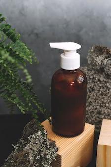 Kosmetyki spa w butelkach z brązowego szkła na naturalnym tle z mchu, drewna, kory drzewa i paproci.