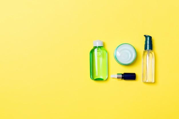 Kosmetyki spa zestaw tubek i słoików śmietany na żółtym tle