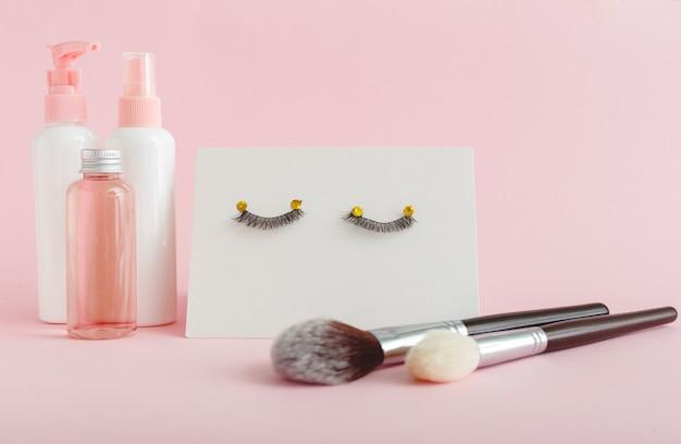 Kosmetyki, sztuczne rzęsy, pędzel do makijażu na różowym tle. produkty kosmetyczne, kosmetyki do makijażu oczu, przedłużanie rzęs, salon kosmetyczny lub koncepcja salonu.
