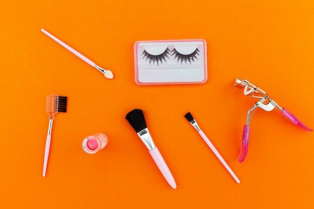 Kosmetyki ustawiający dla kobiet odizolowywać na pomarańcze papieru tle