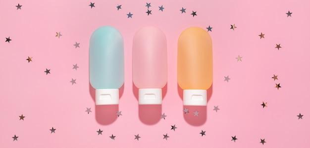 Kosmetyki w minimalistycznych tubkach z brokatowymi gwiazdkami na różowym tle. koncepcja pielęgnacji ciała i twarzy, nawilżający krem i balsam