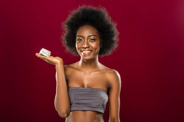 Kosmetyki wysokiej jakości. przyjemna wesoła kobieta uśmiecha się do ciebie stojąc z butelką z kremem