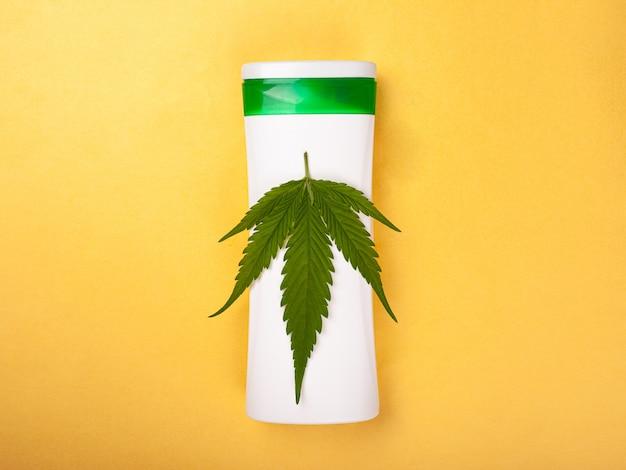 Kosmetyki z ekstraktem z marihuany. pielęgnacja skóry, uroda, liść konopi na białej butelce na żółtym tle widok z góry.
