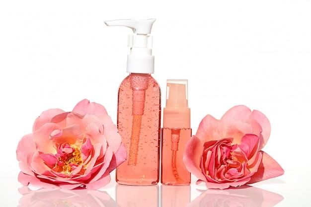 Kosmetyki z ekstraktem z róży. żel i tonik w kolorze różowym z ekstraktem z róży w plastikowej butelce i frotte duża różowa róża kwiatowa. koncepcja botanicznych kosmetyków naturalnych