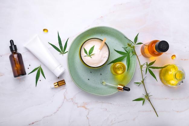 Kosmetyki z olejem konopnym na turkusowym talerzu na jasnym marmurowym tle makieta przestrzeni kopii