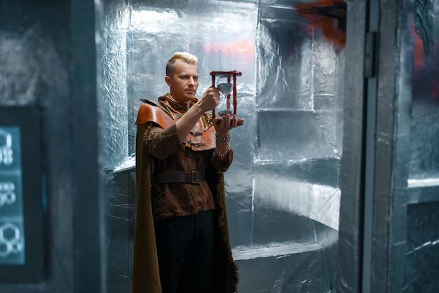 Kosmiczny podróżnik trzyma klepsydrę w foliowych ścianach futurystycznego statku kosmicznego. statek kosmiczny fantasy do podróży międzygwiezdnych, nauki i technologii przyszłości