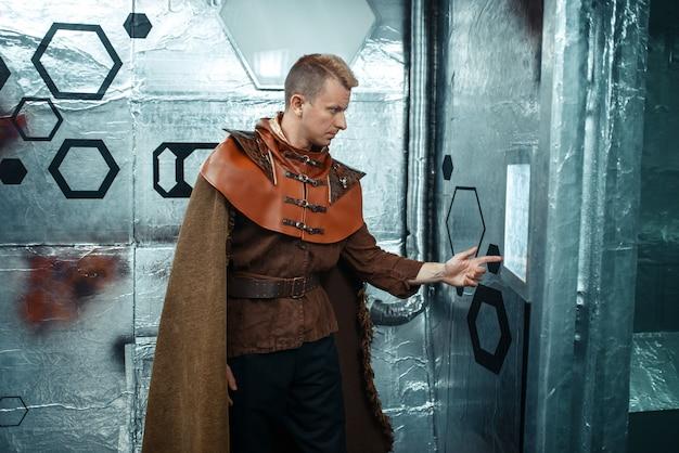 Kosmiczny podróżnik wprowadza dane na tablicę teleportacji, statek kosmiczny z foliowymi ścianami. statek kosmiczny fantasy do podróży międzygwiezdnych, nauki i technologii przyszłości