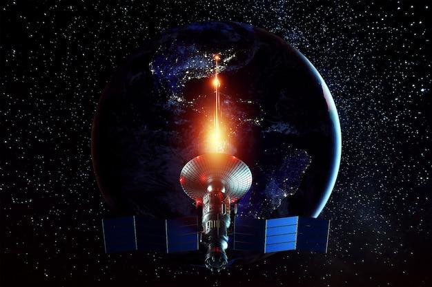 Kosmiczny satelita wojskowy, broń w kosmosie strzela laserem w ścianę ziemi. atak, technologia, wojna kosmiczna. mieszane medium, kopia przestrzeń. zdjęcie dostarczone przez nasa.