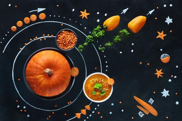 Kosmiczny układ słoneczny dyni z zupą z marchwi, pieprzu i soczewicy, koncepcja płaskiego leżała zdrowa żywność