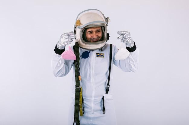 Kosmonauta mężczyzna w skafandrze i hełmie, trzymając dwie maski fpp2 na białym tle. covid-19 i koncepcja wirusa