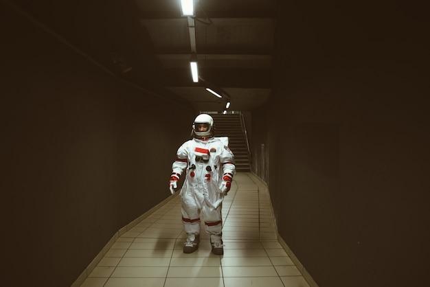 Kosmonauta na futurystycznej stacji mężczyzna w skafandrze kosmicznym wychodzący do pracy i wsiadający do pociągu