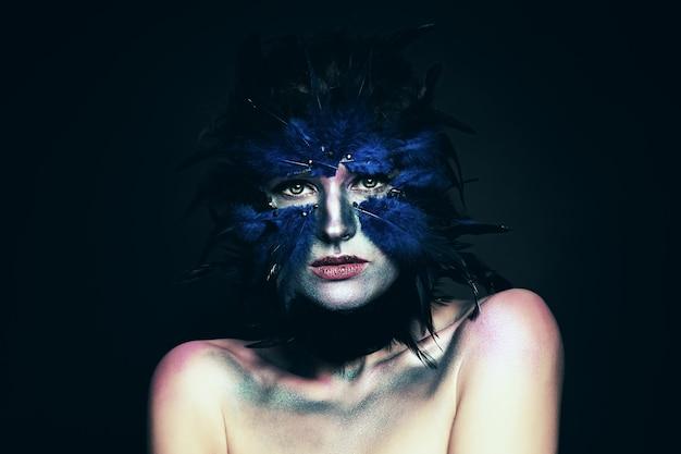 Kostium karnawałowy. kobieta z fantazja makeup. maska niebieskiego ptaka