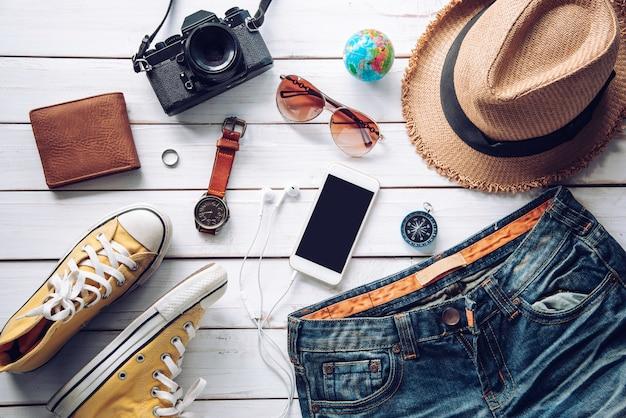 Kostiumy na akcesoria podróżne. paszporty, bagaż, koszt map podróży przygotowanych na podróż, na białej drewnianej podłodze